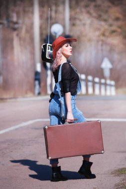Young traveling woman with suitcase walking on the road traveling hitchhiking