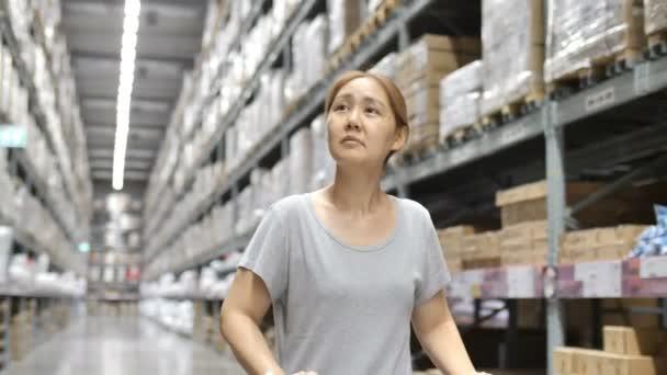 4 k zpomalené Asijské žena jízdy nákupního vozíku ve skladu, výběr nového nábytku