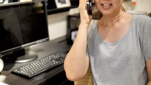 4k asiatische Frau spricht per Smartphone im Büro