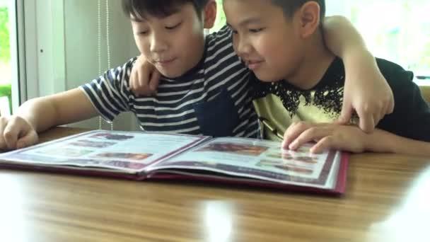 Šťastné Asijské dítě vypadat a zvolte v menu knihy.