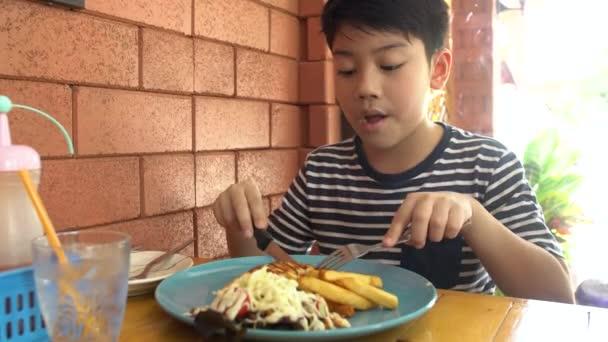 kleines asiatisches Kind isst Schweinesteak im Restaurant, glücklicher asiatischer Junge genießt es beim Essen.