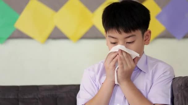 Kleines asiatisches Kind krank mit Grippe niesen und mit Gewebepapier reinigen