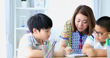 Mother and child son draws are engaged in creativity at home