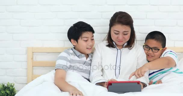 Happy asian family mother with her son playing game with tablet computer on the bed at home .