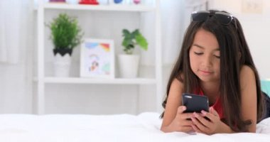 Happy asian cute girl playing on smart phone with smile face at home.