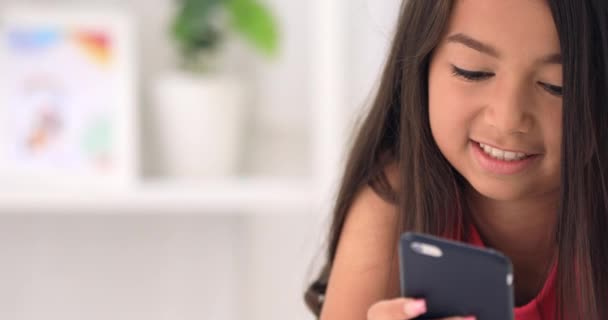 Happy asijské roztomilý dívka hraje na chytrého telefonu s tváří úsměv doma.