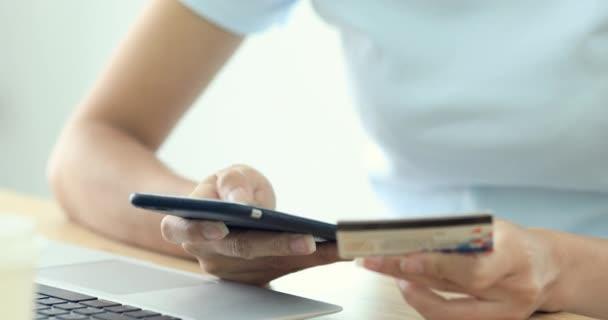 Online vásárlás. Fiatal kaukázusi kezek felvásárlási áruk-az Internet a smartphone-val a hitelkártya.