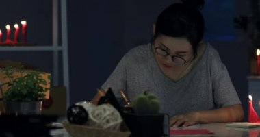 Woman wrapping Christmas or other holiday handmade present in paper . Making bow at gift box