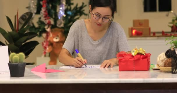 Close up of asian cute girl writing happy card and show paper with smile face