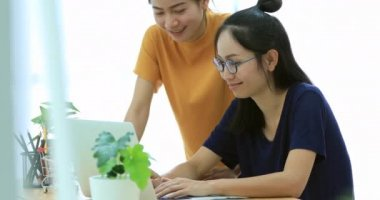 Two beautiful asian business women are working in a light and modern office and looking at laptop computer. They are discussing possibilities for future business ventures.