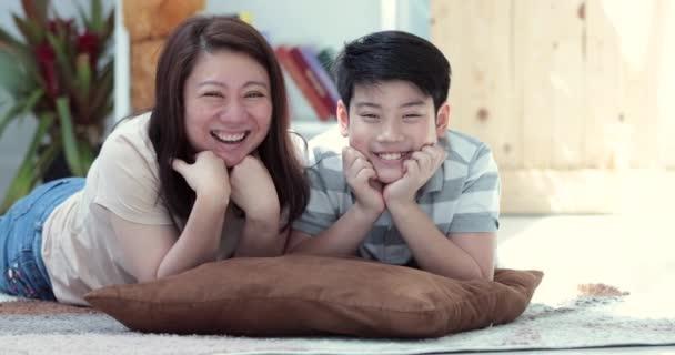 Portrét asijské rodiny matka a syn při pohledu na fotoaparát a společná jednání na tváři