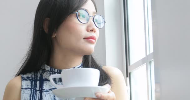 Detailní pohled na ženské ruce, přičemž bílý hrnek s horkou kávou z tabulky. Pak kamera se pohybuje s šálkem a tato žena začne pít kávu.