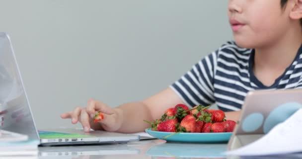 Asijské chlapce jí doma jahody a pomocí poznámkového bloku. Kauzální životní styl.