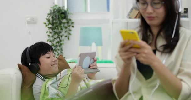 Young asian Woman relaxing and listening to music with young boy playing on tablet computer in the living room.