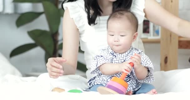 Young beautiful asian woman teaching and play with child at home with smile face.