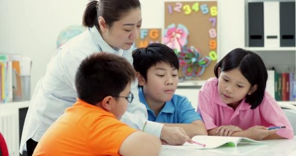 Mladá Asijská učitelka pomáhá mladým školní děti ve třídě, zblízka