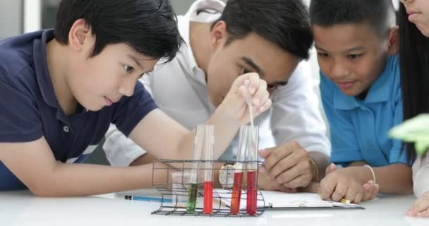 Teacher pouring chemical into test tube with his student in classroom .