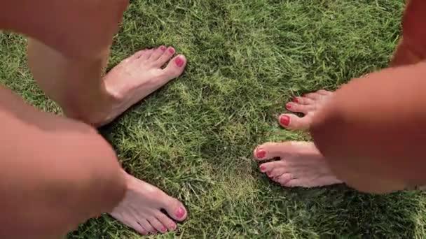 zwei Paar weibliche Füße mit rosa und roten Nägeln stehen sich auf dem grünen Gras gegenüber und wackeln mit den Fingern, Draufsicht