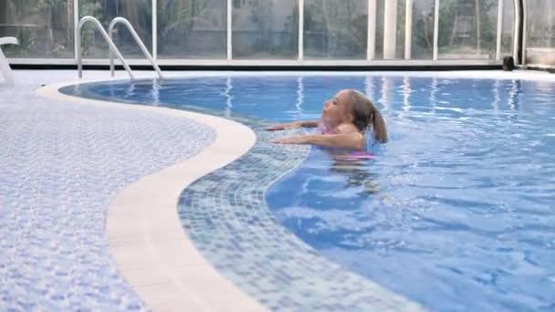 Blondýnka v růžových plavkách legračně vychází z bazénu s průzračnou modrou vodou.