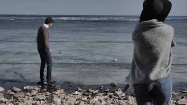 Mladý pár kráčí po skalnatém břehu u skály u řeky pokryté ledem, slunečný jarní den
