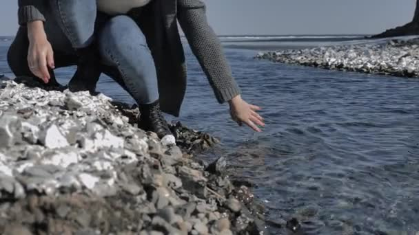 Young girl moisturizes her hand, dipping in clear water on a rocky shore, sunny day