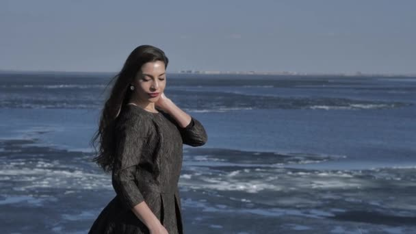 A young girl in a black dress strokes her hair, in the background the ocean, sunny day