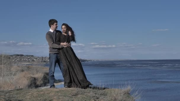 Young couple dressed in dark walks along the seashore, sunny day.