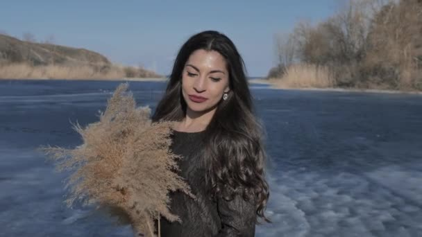 A young Caucasian girl in a black dress holds a cane bouquet in her hands, in the background a river covered with blue ice, a sunny day