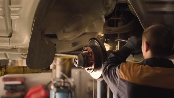 Asijský muž opravuje podvozek starého auta zvednutého na výtahu v dílně, zblízka.