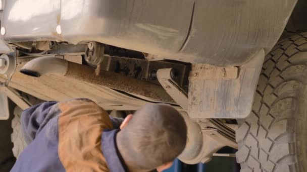 An Asian man is repairing the chassis of an old car lifted on a lift in a workshop, close-up.