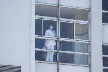 Yeni koronavirüs kriziyle ilgilenen sağlık çalışanları 26 Mart 2020 'de İspanya' nın kuzeybatısındaki Coruna Üniversitesi Hastanesi 'nin penceresinden baktılar.