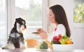 Žena krmení psa na kuchyňském stole