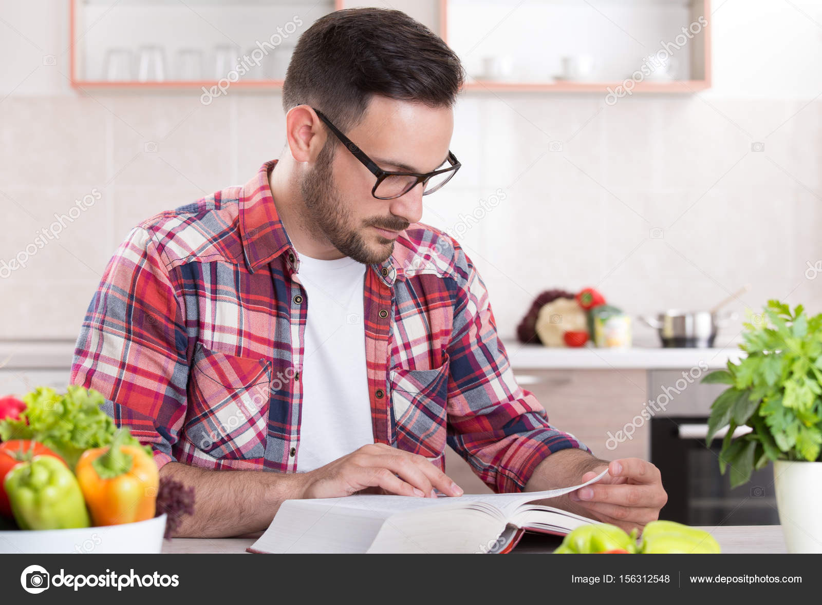 Man reading recipe book in kitchen stock photo budabar 156312548 man reading recipe book in kitchen stock photo forumfinder Image collections