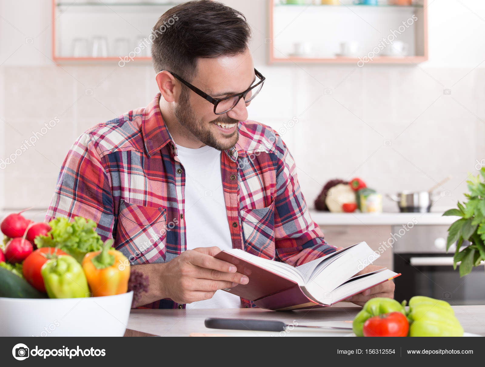 Man reading recipe book in kitchen stock photo budabar 156312554 man reading recipe book in kitchen stock photo forumfinder Image collections