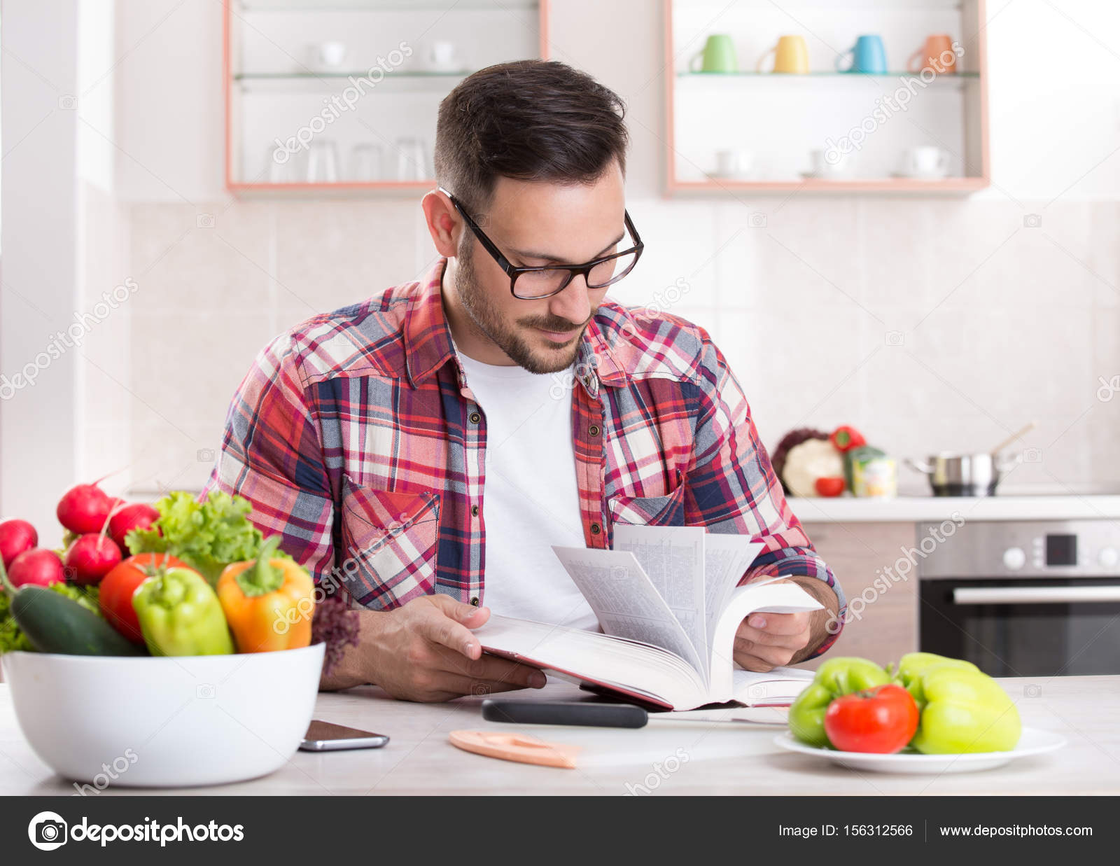 Man reading recipe book in kitchen stock photo budabar 156312566 man reading recipe book in kitchen stock photo forumfinder Image collections