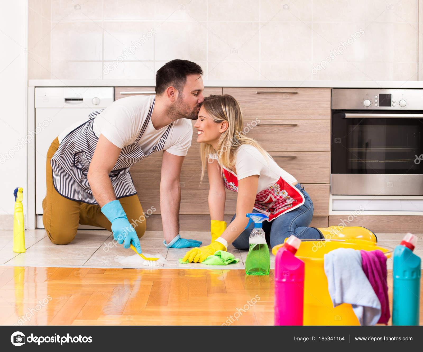 Joven pareja limpiando la casa juntos y tener momentos tiernos ...