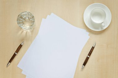 Sheet of paper, pens, glass of water and cup for coffee