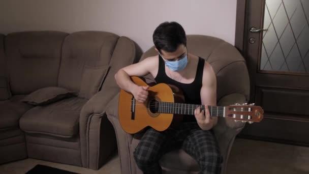 Kaukasischer Mann mit medizinischer Maske spielt auf der Couch sitzend selbstisoliert Quarantäne. Junger Mann spielt Gitarre