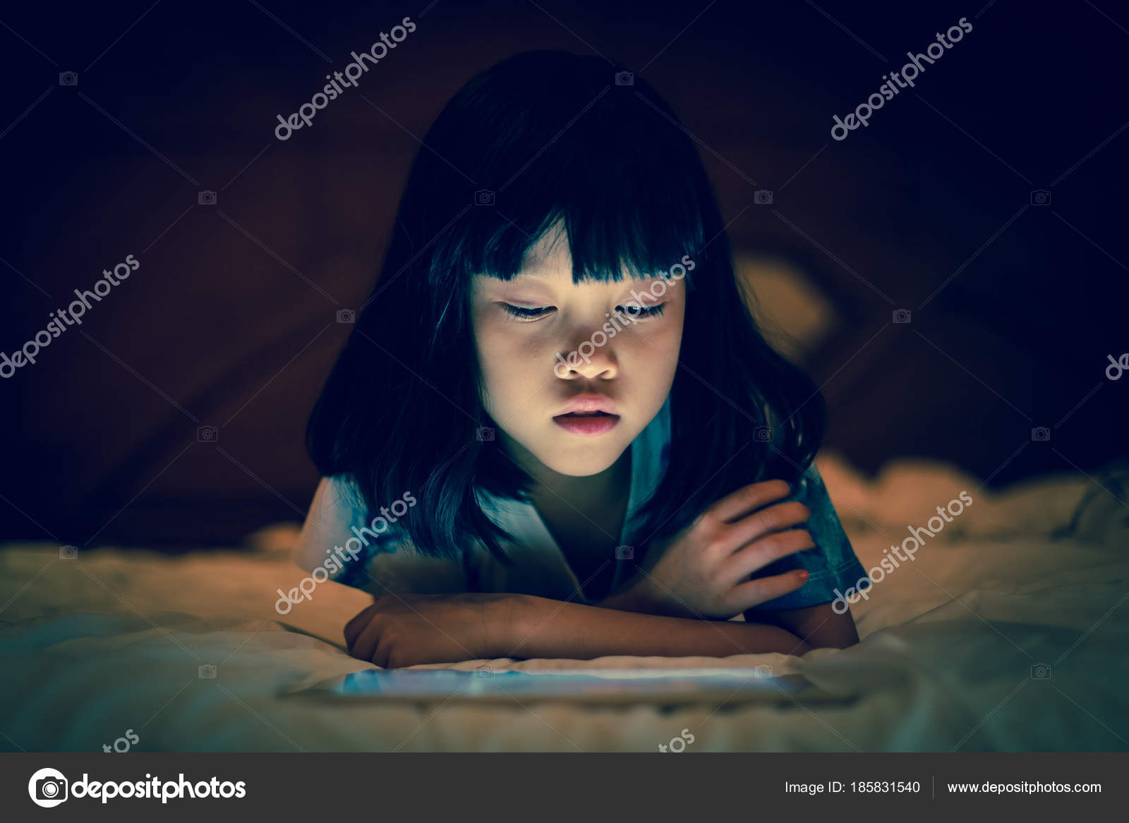 Asian Kid Girl Using Tablet Watching Movie While Lying On Bed In Dark Background Of Bedroom Bright Light Screen Reflex Her Face Photo By Vinnstock