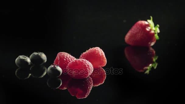 Fresh berries fruits on black background.