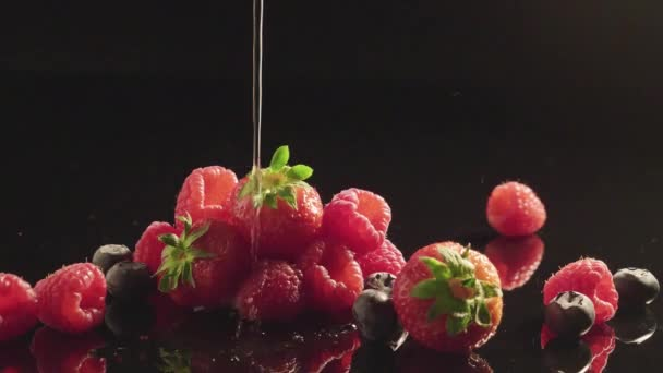 Pouring water on fresh berries fruits.