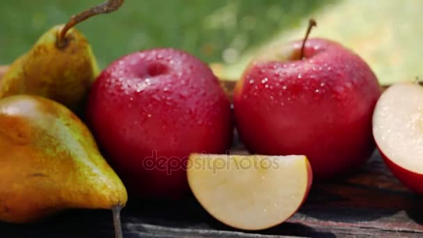 Čerstvá jablka a hrušky s vodou kapky na dřevěný stůl v zahradě