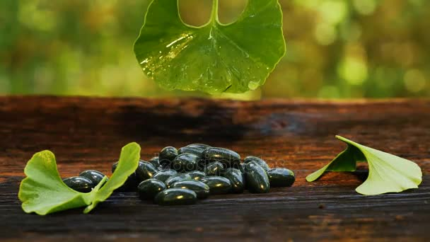 Water Drop Falling From Ginkgo Leaf In Slow Motion on gel capsules. Wooden table with ginkgo leaves and capsules