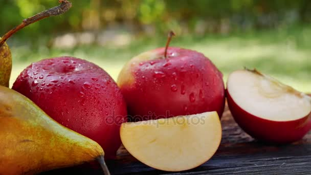 Pohyb kamery na čerstvé ovoce s kapičkami vody. Jablka a hrušky s kapkami vody