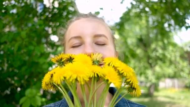 Usmívající se žena držící květinovou kytici pampelišek. žena a žluté květy