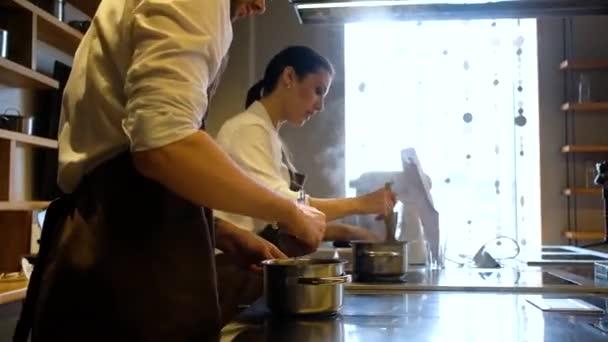 Mann und Frau kochen in der Küche einer Bäckerei. Berufsvorbereitung Konditorei