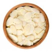 Plátky oloupaných mandlí v dřevěné misce nad bílá
