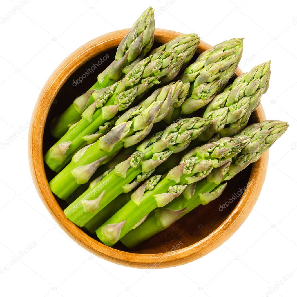 Fresh green asparagus tips in wooden bowl