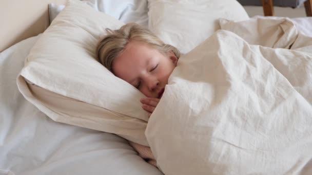 Dívka spí přikrytá přikrývkou v posteli. Pohled shora