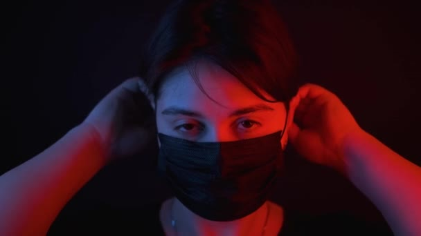 Caucasian girl puts on black medical mask,red and blue neon light on face